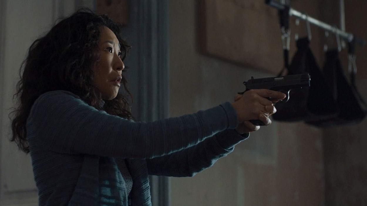 Une femme apeurée pointe un pistolet en direction de quelque chose qui se trouve hors du cadre de la photo.