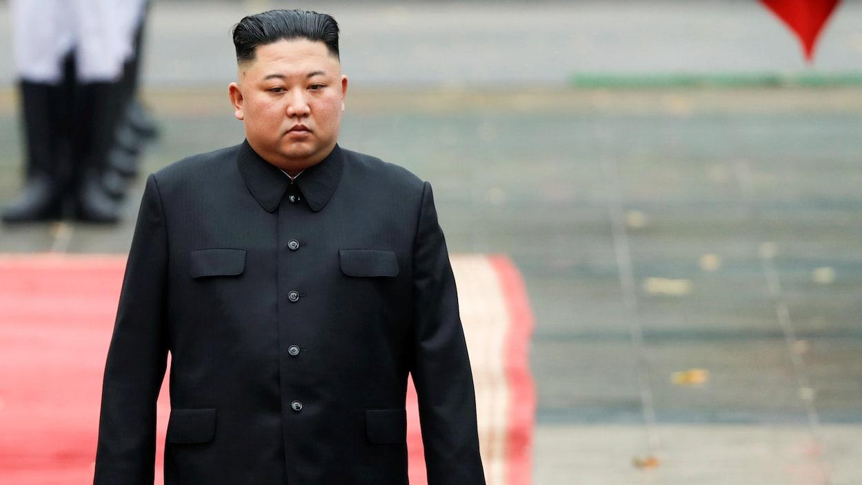 Kim Jong-un marche sur un tapis rouge.