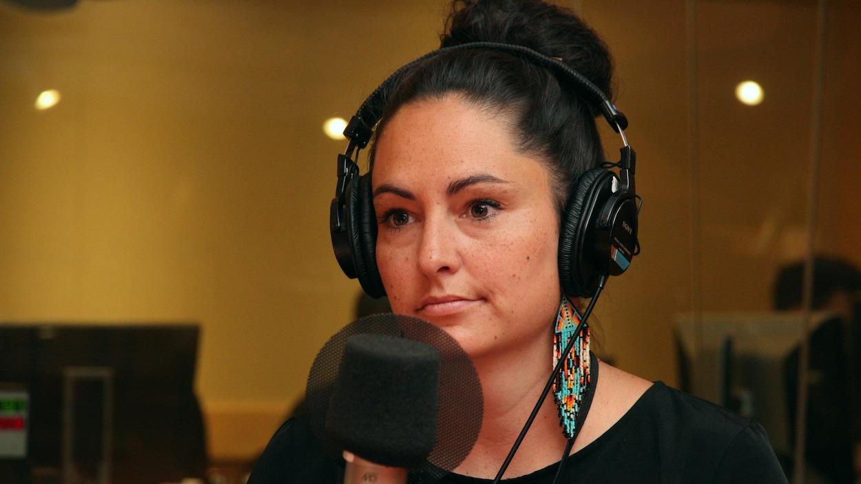 Une femme portant un casque d'écoute et des boucles d'oreilles autochtones est derrière un micro.