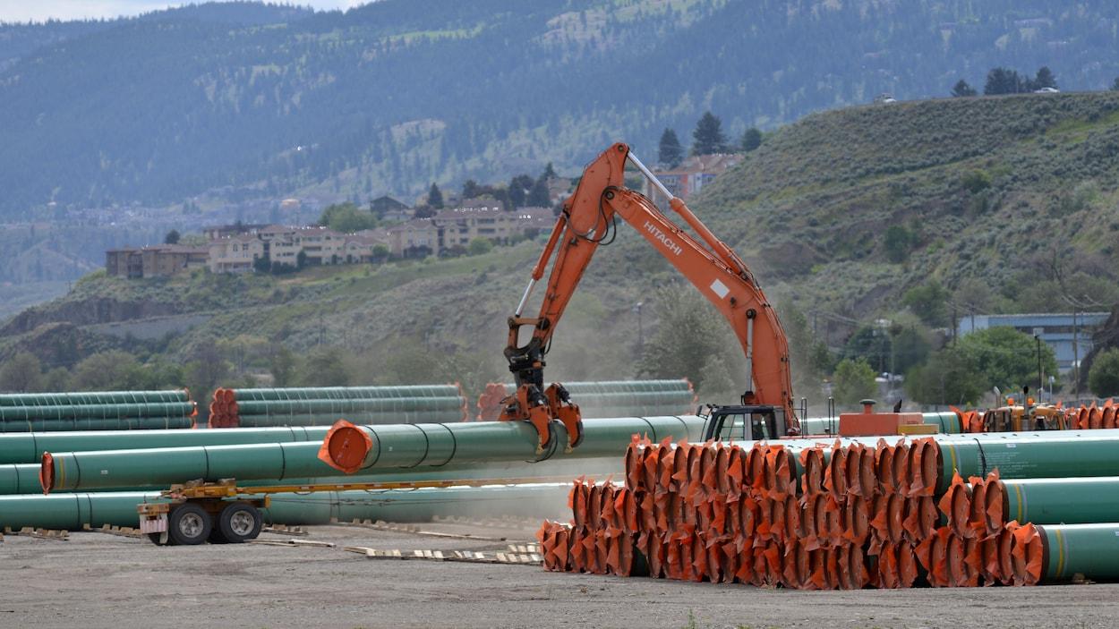Une pelle mécanique déplace de longs tuyaux sur un terrain sablonneux devant une colline.