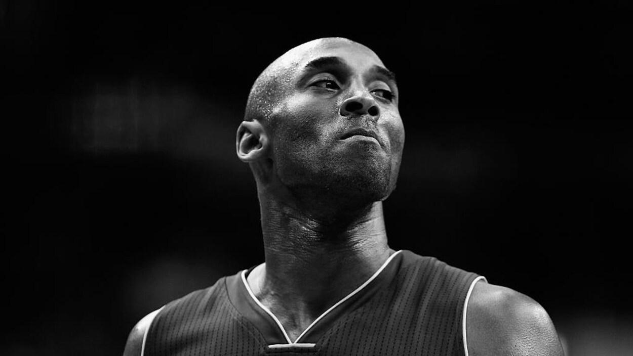 Portrait en noir et blanc du sportif, qui porte un chandail de basketball