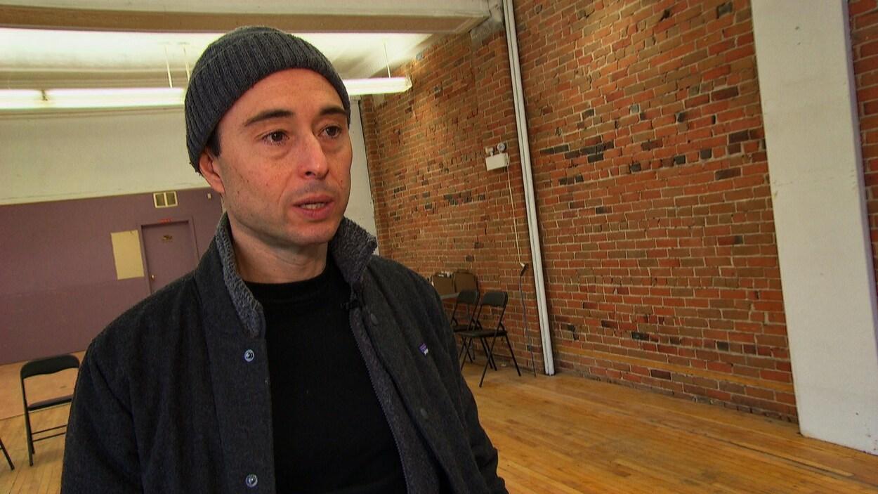 Koby Smutylo répond aux questions d'une journaliste dans un local vide.
