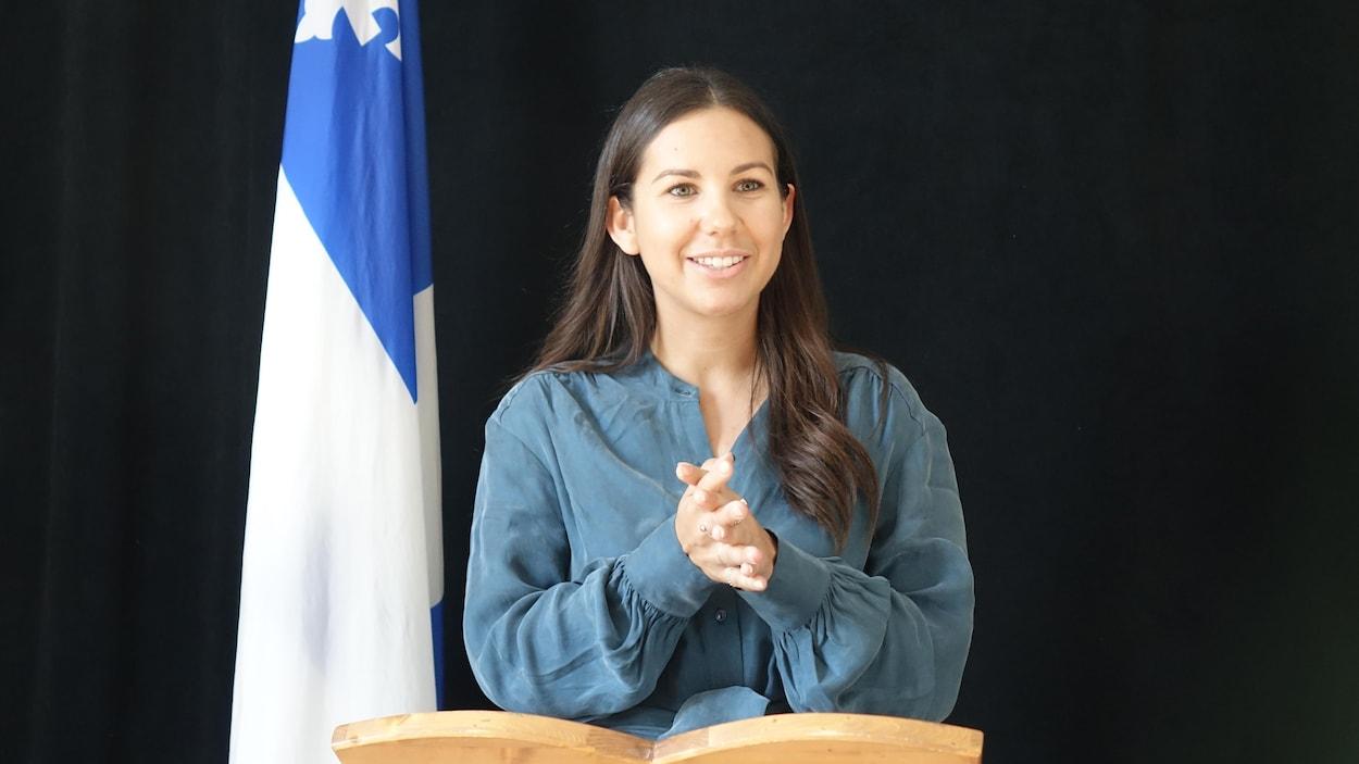 Kristina Michaud sourit et se tient devant un drapeau québécois lors du lancement de sa campagne électorale.
