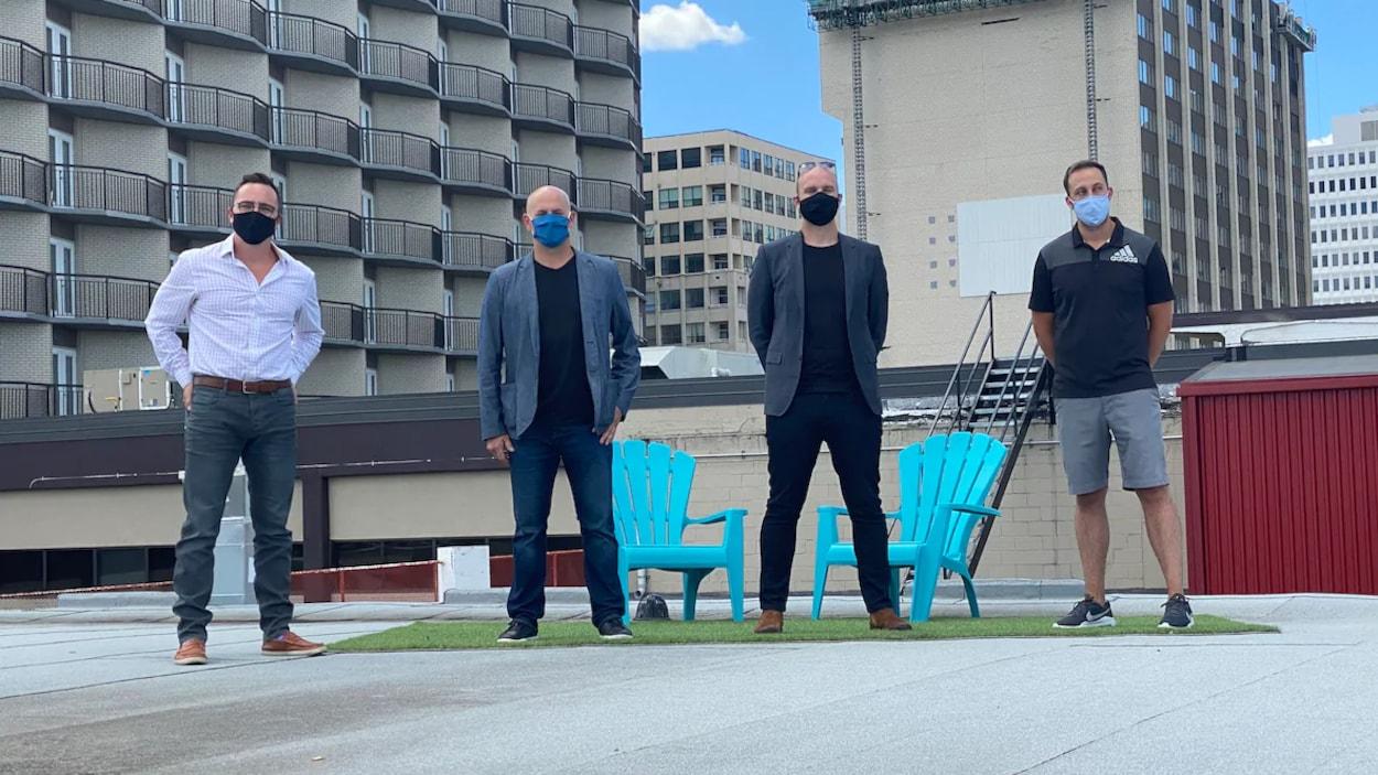 Quatre hommes alignés les uns à côté des autres sur un toit au centre-ville de Regina. Ils portent tous un masque.