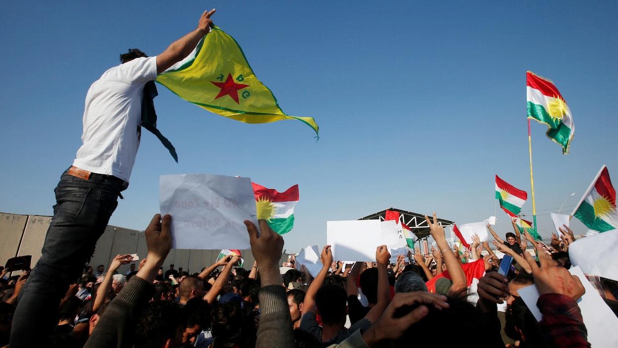 Une foule kurde brandissant des drapeaux et des affiches à bout de bras.