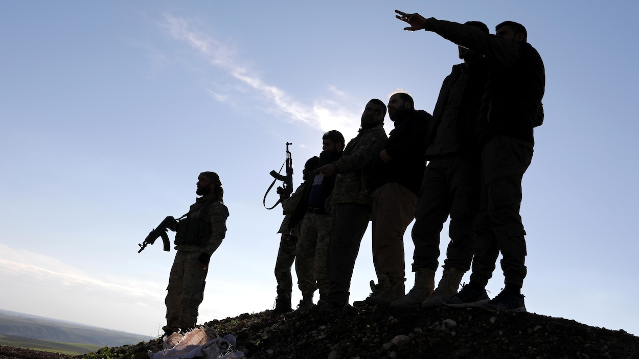 Des rebelles syriens armés, appuyés par la Turquie, sont positionnés dans les environs de la ville de Manbij, sous contrôle kurde.