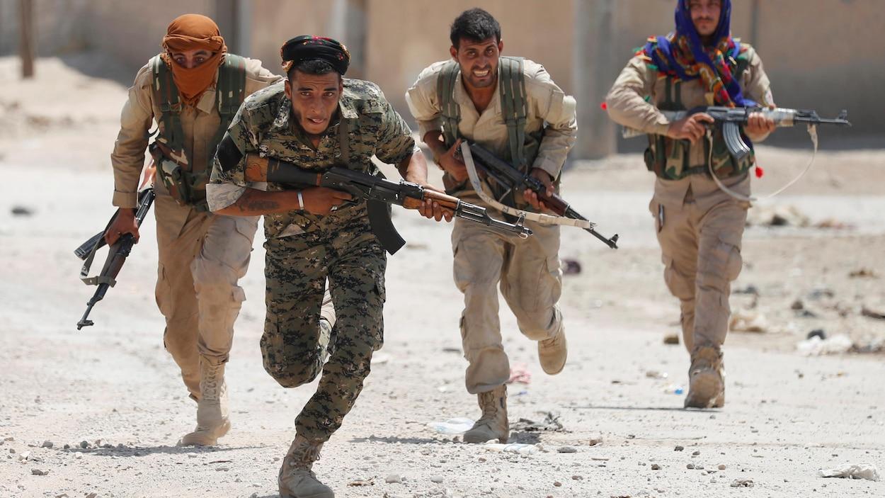 Quatre combattants des YPG courent dans une rue de Raqqa, en juillet 2017.