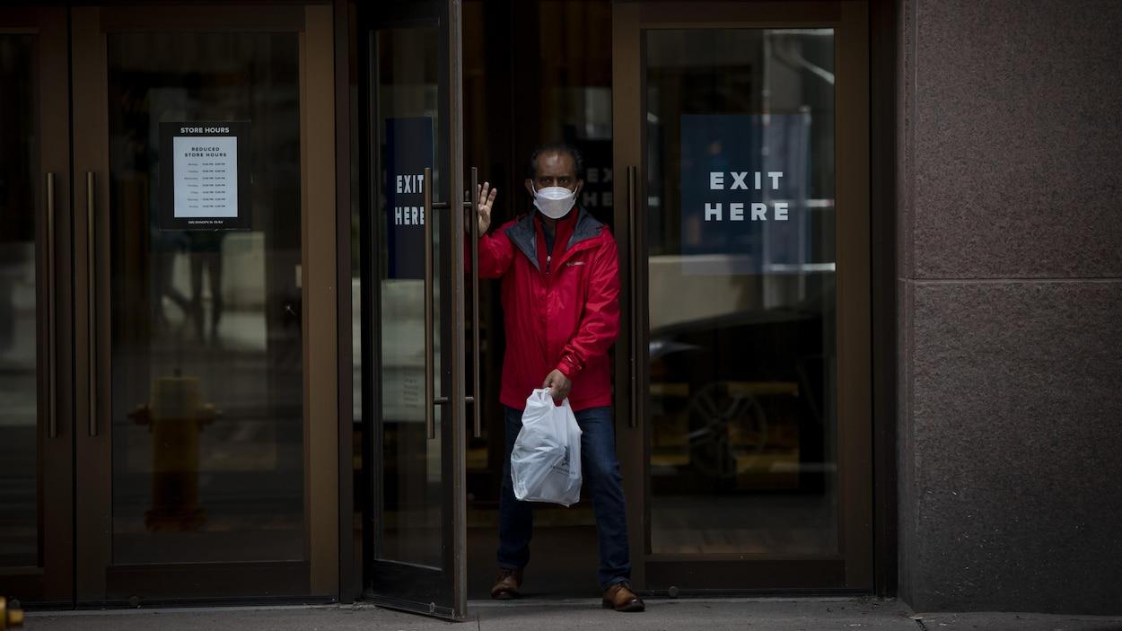 Un homme qui porte un masque sort du grand magasin La Baie au centre-ville de Toronto.