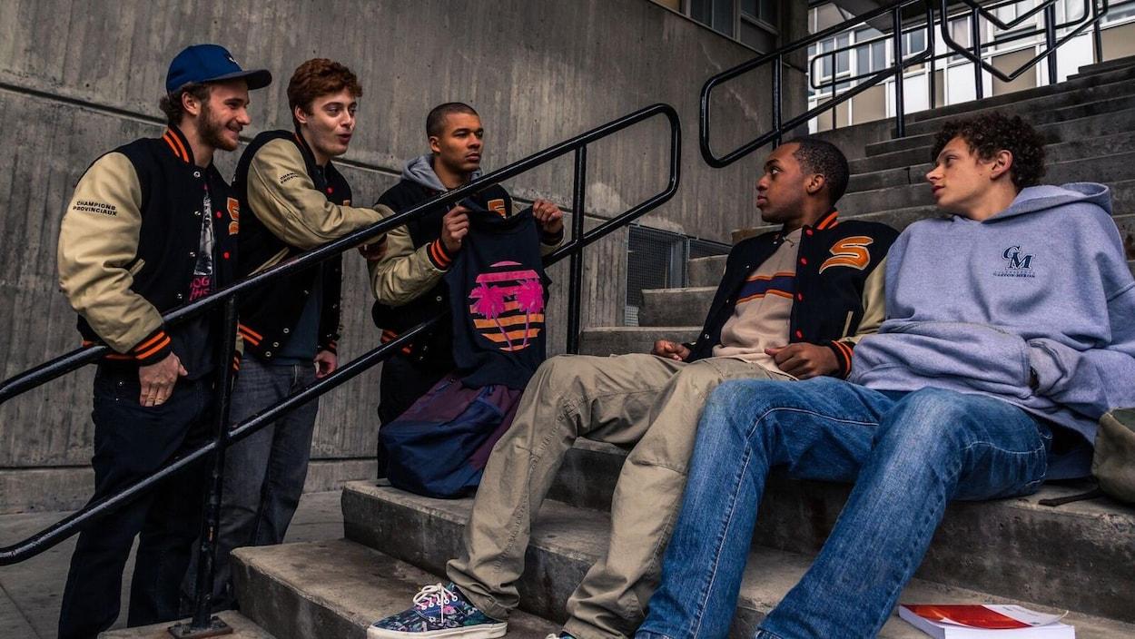 Lévi Doré et Jonathan St-Armand sont assis sur un escalier. Sur le côté, Karl Walcott, Charles-Antoine Perreault et Gabriel Tremblay les regardent et leur parlent dans une scène de  La chute de Sparte .