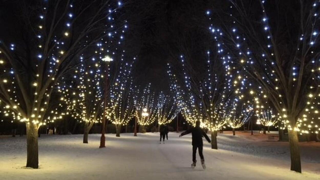 Des gens patinent, des lumières dans des arbres
