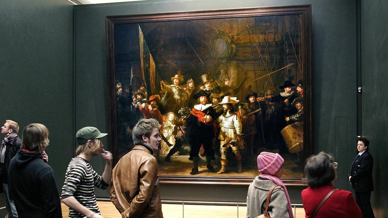 Plusieurs personnes se trouvent près du tableau «La ronde de nuit», peint par Rembrandt.