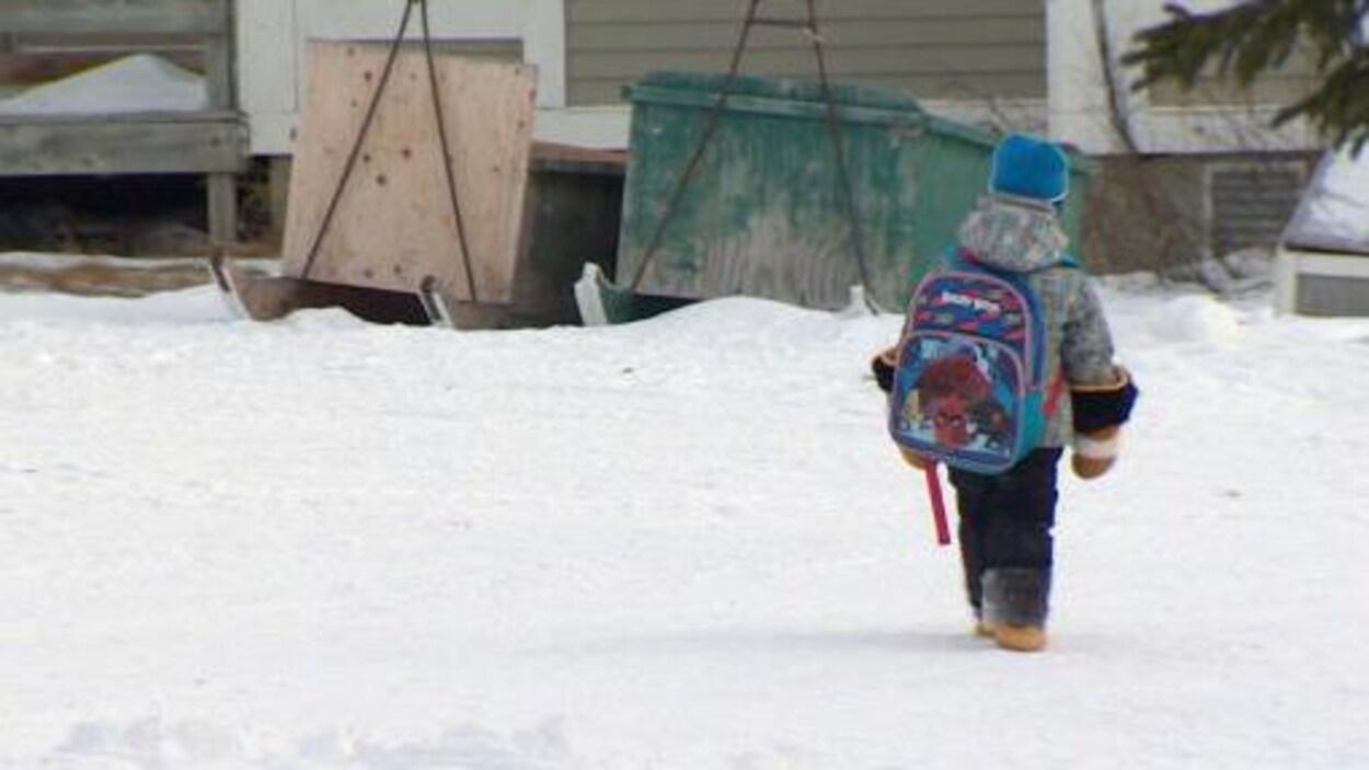 Un enfant marche dans la neige avec son sac d'école.