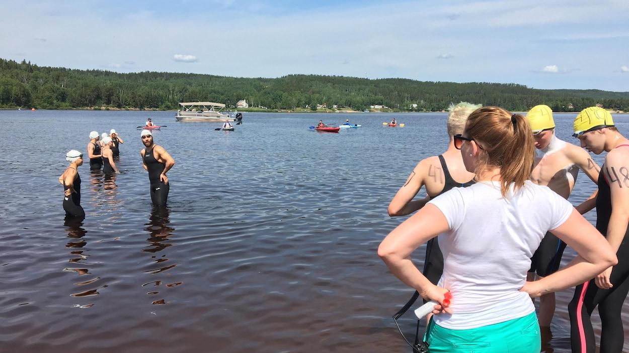 Des nageurs sont avancés dans les eaux du lac à Jim jusqu'aux genoux.