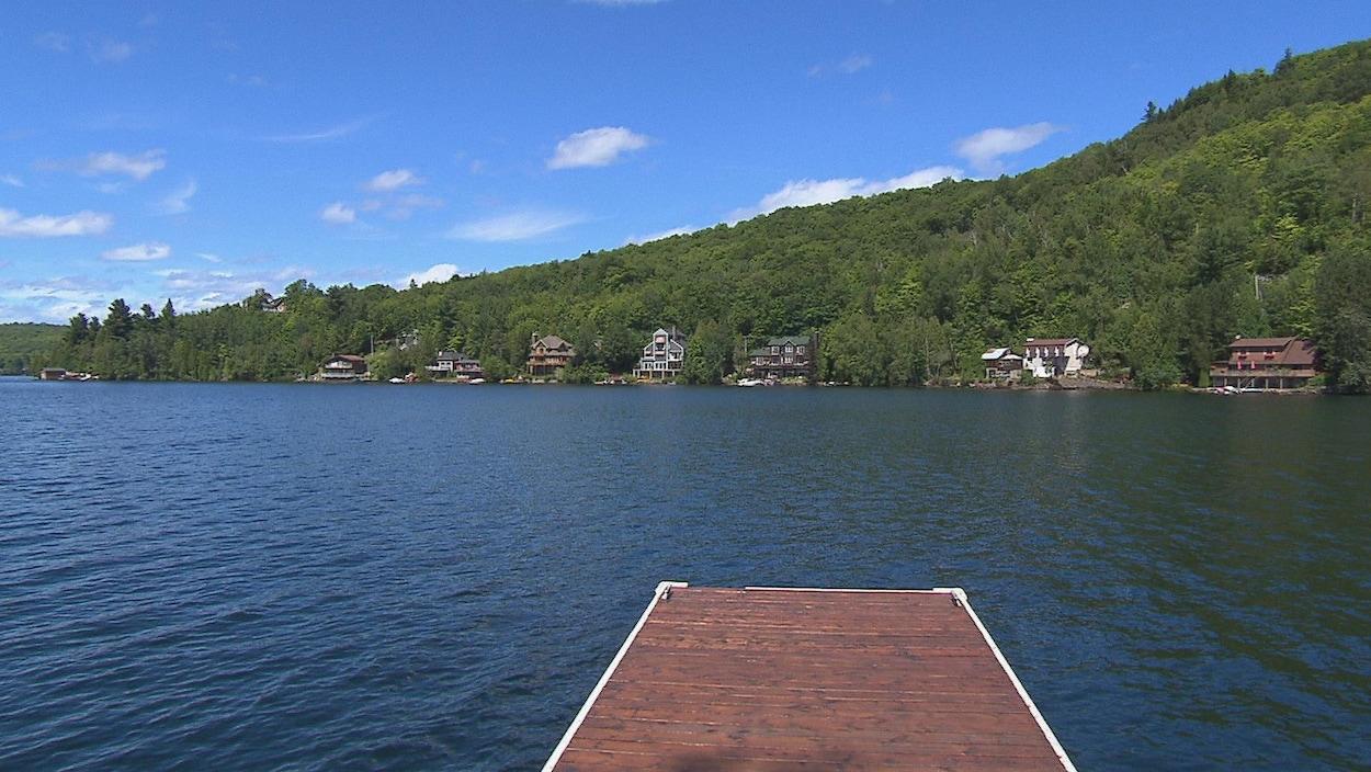 Un quai s'avance dans le lac. Au loin, en bordure du plan d'eau, on distingue des résidences.