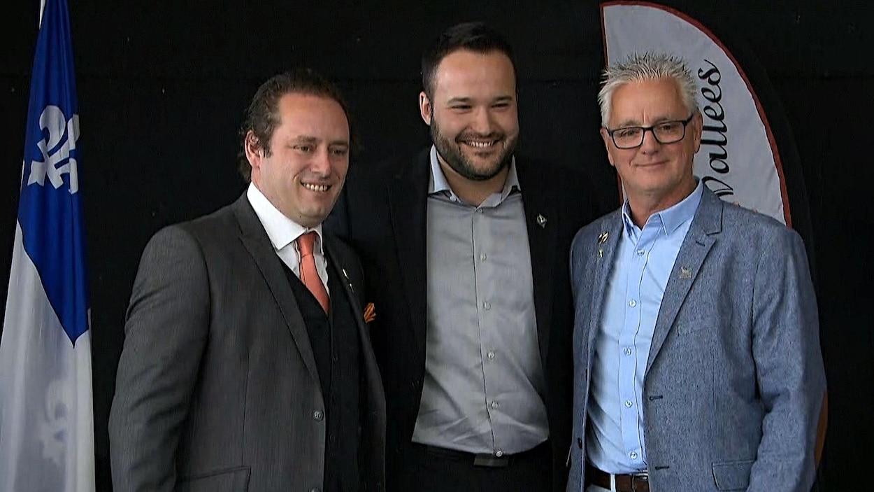 Les trois hommes, côte-à-côte, sourient sur l'estrade en regardant les photographes.