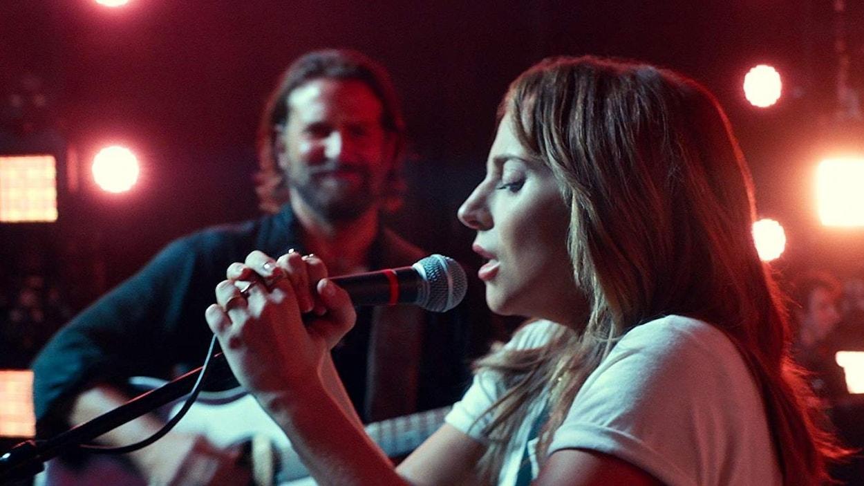 Bradley Cooper, qui joue de la guitare, et Lady Gaga, qui chante au micro, dans le film A Star Is Born.