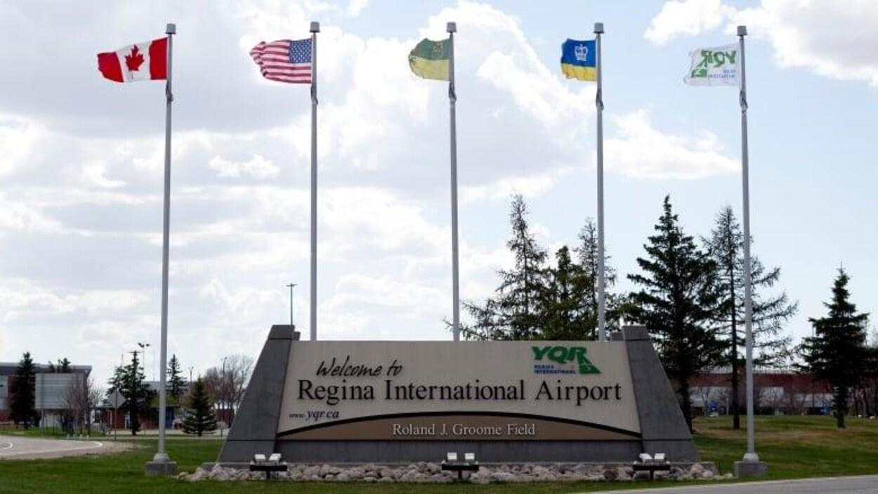 Vue de l'entrée de l'aéroport international de Regina avec des drapeaux qui flottent.