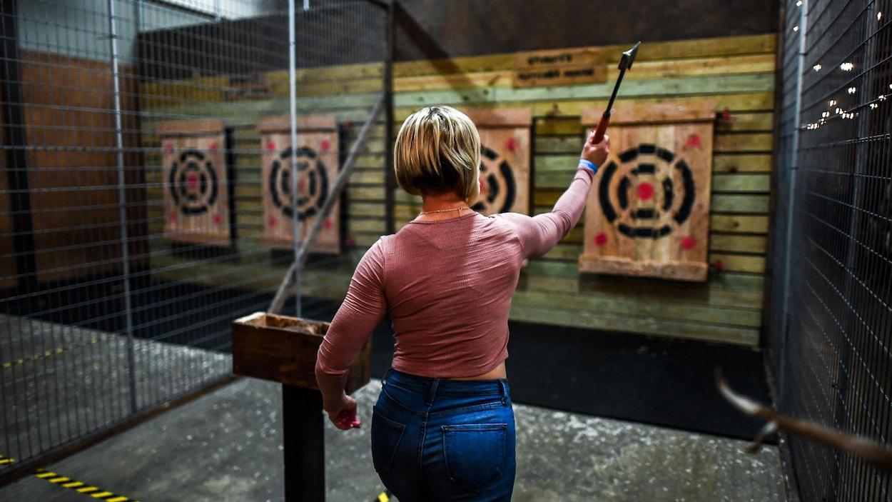 Une femme lance une hache en direction d'une cible.