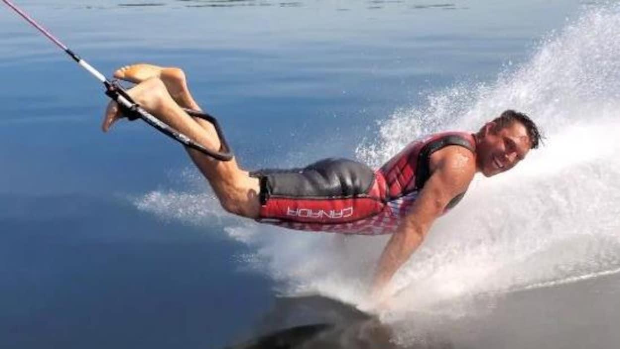 Un homme accroché à une corde de ski nautique par les pieds fait des pompes directement sur l'eau.