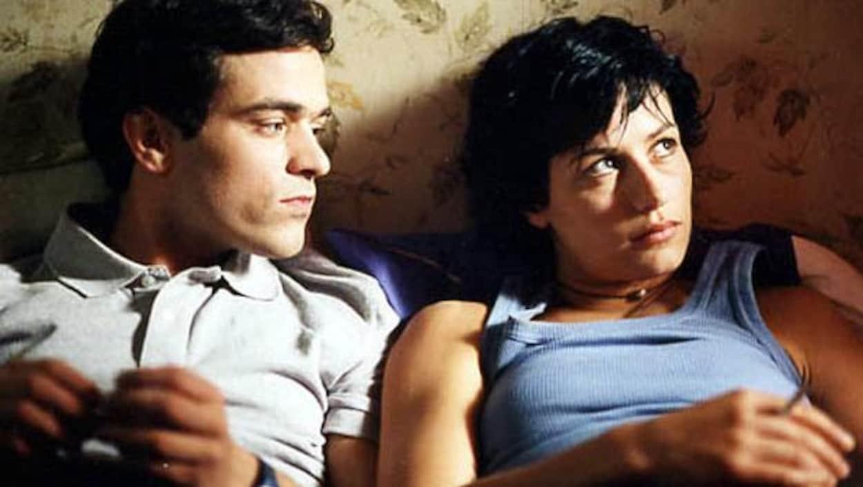Un homme et une femme sont allongés côte à côte dans un lit.