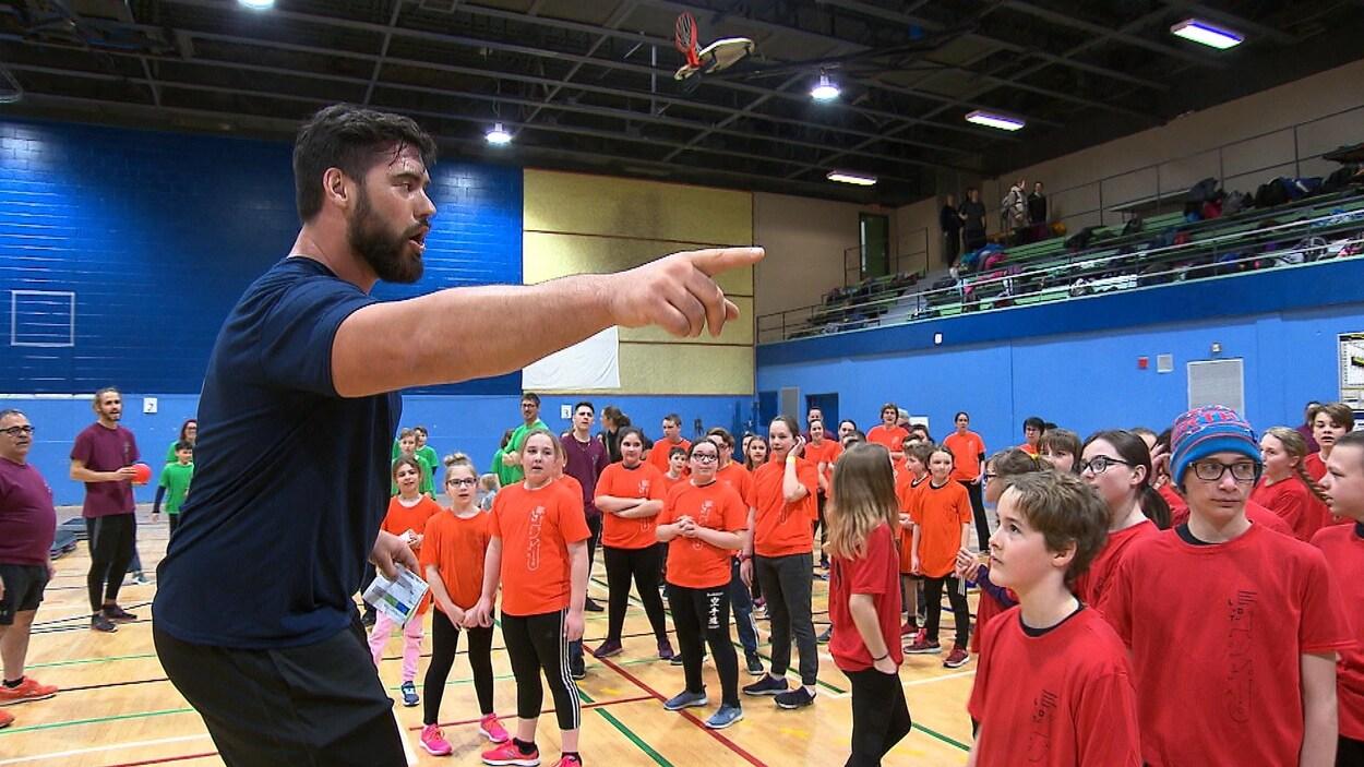 Laurent Duvernay-Tardif parle à un groupe d'élèves assemblés devant lui, dans un gymnase.