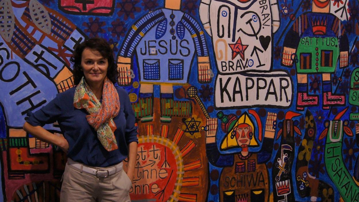 L'historienne de l'art Lucienne Peiry posant devant une murale colorée.