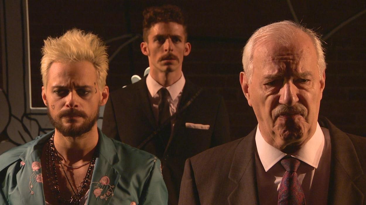 sur scène trois des comédiens du menteur en train de jouer, les traits sérieux