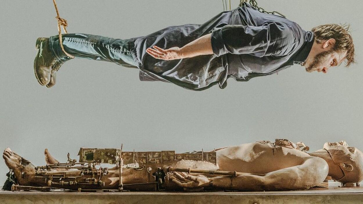 Un homme est suspendu horizontalement par des cordes et regarde un mannequin en bois avec des broches en métal sur les jambes qui est allongé sur une table