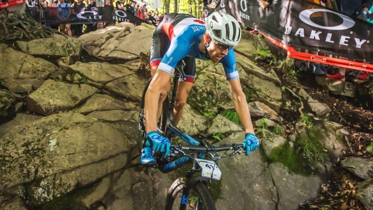 Un cycliste descend une pente dans un sentier se trouvant dans une zone boisée.