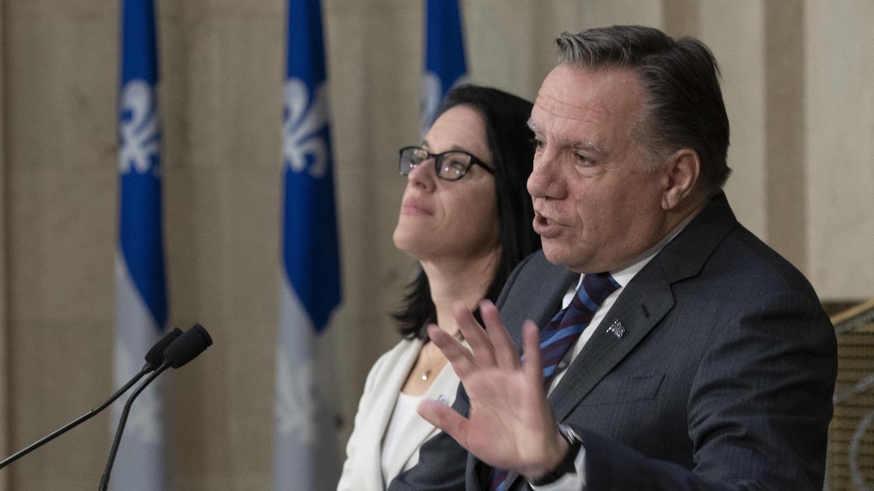 François Legault et la ministre responsable des Relations canadiennes et de la Francophonie canadienne, Sonia LeBel derrière un micro.