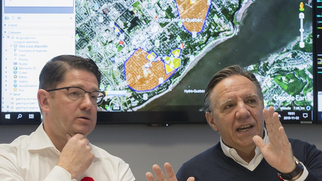 Le premier ministre Francois Legault et le PDG d'Hydro-Québec Eric Martel devant une carte du Québec indiquant les pannes.