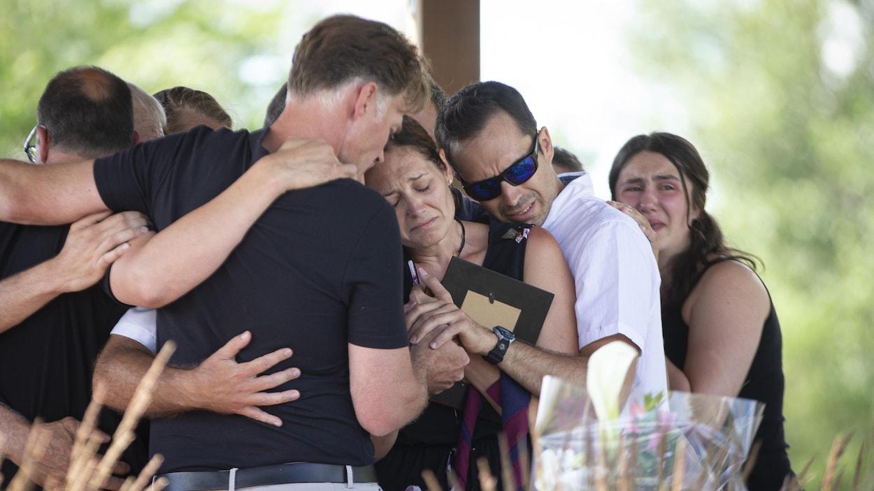 Une femme en pleurs entourée de ses proches.