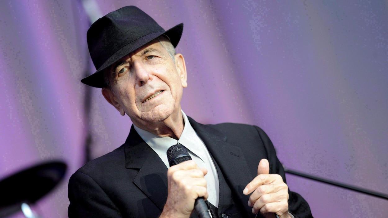 Le chanteur Leonard Cohen portant un chapeau noir et un complet, micro en main, sur une scène extérieure.