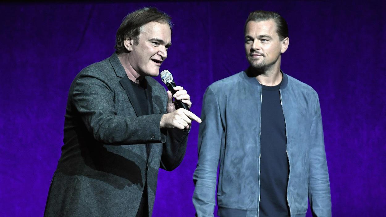 Quentin Tarantino s'adresse au public du CinemaCon pendant que Leonardo DiCaprio le regarde.
