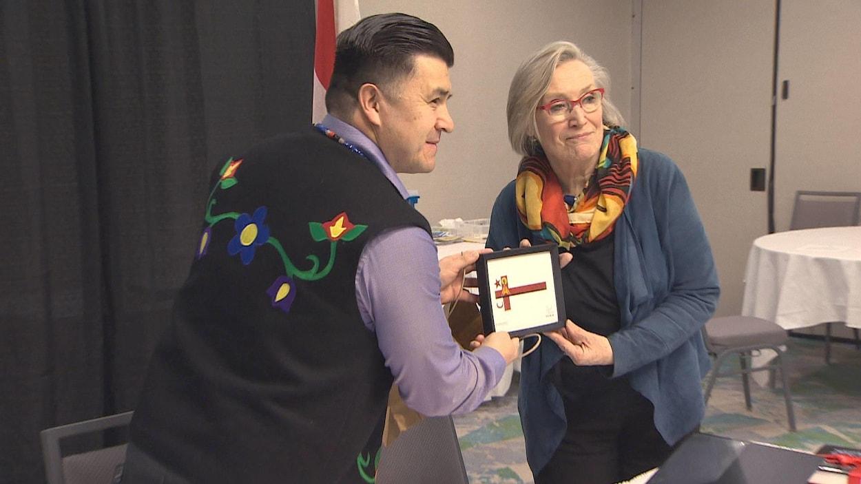 Le chef Leroy Denny et la ministre Carolyn Bennett échangent des cadeaux lors de l'annonce de la signature d'une entente sur l'éducation le 14 mars 2019 en Nouvelle-Écosse.