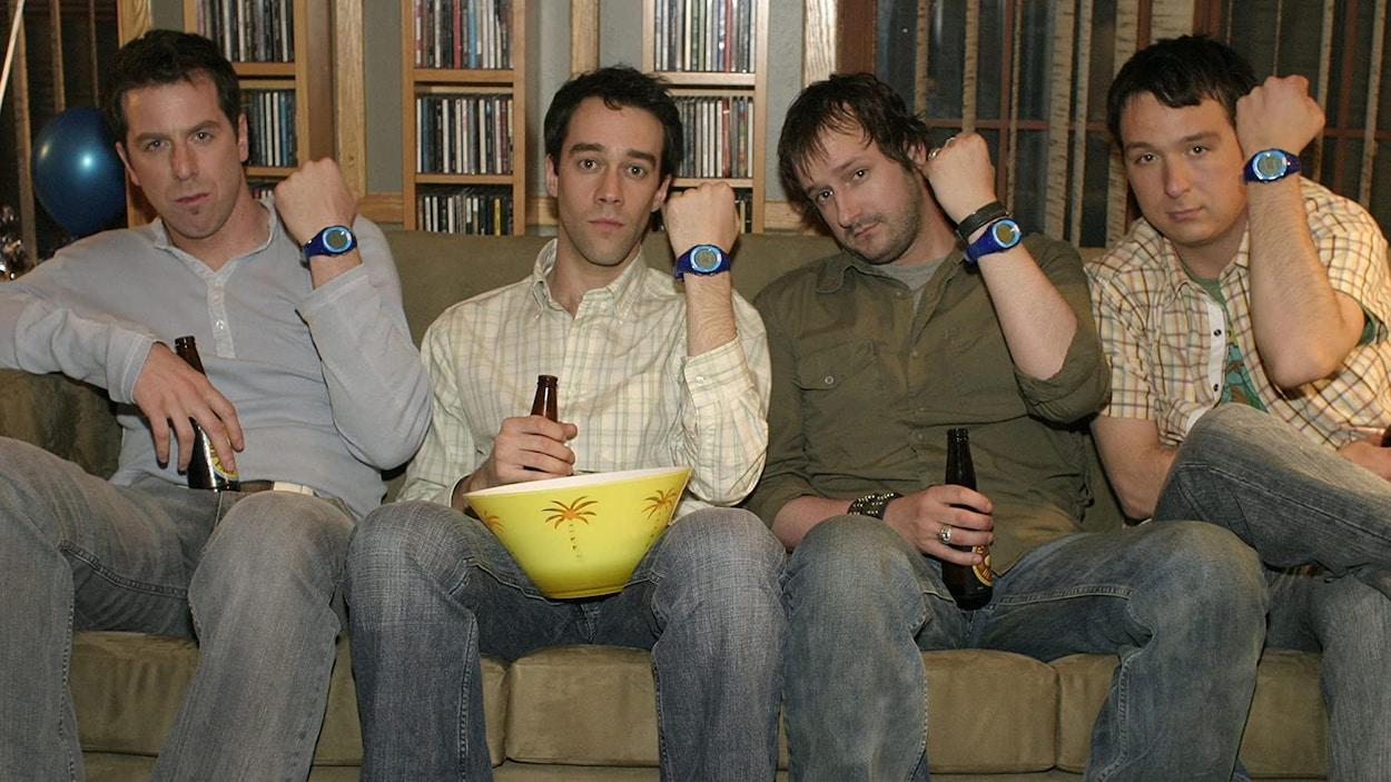 Les quatre hommes sont assis sur un divan et montrent leur montre.