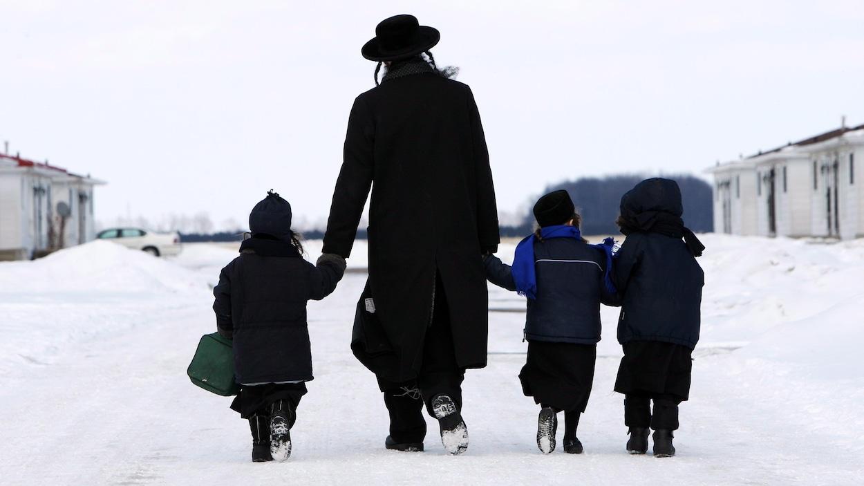 Un homme tient des enfants par la main.
