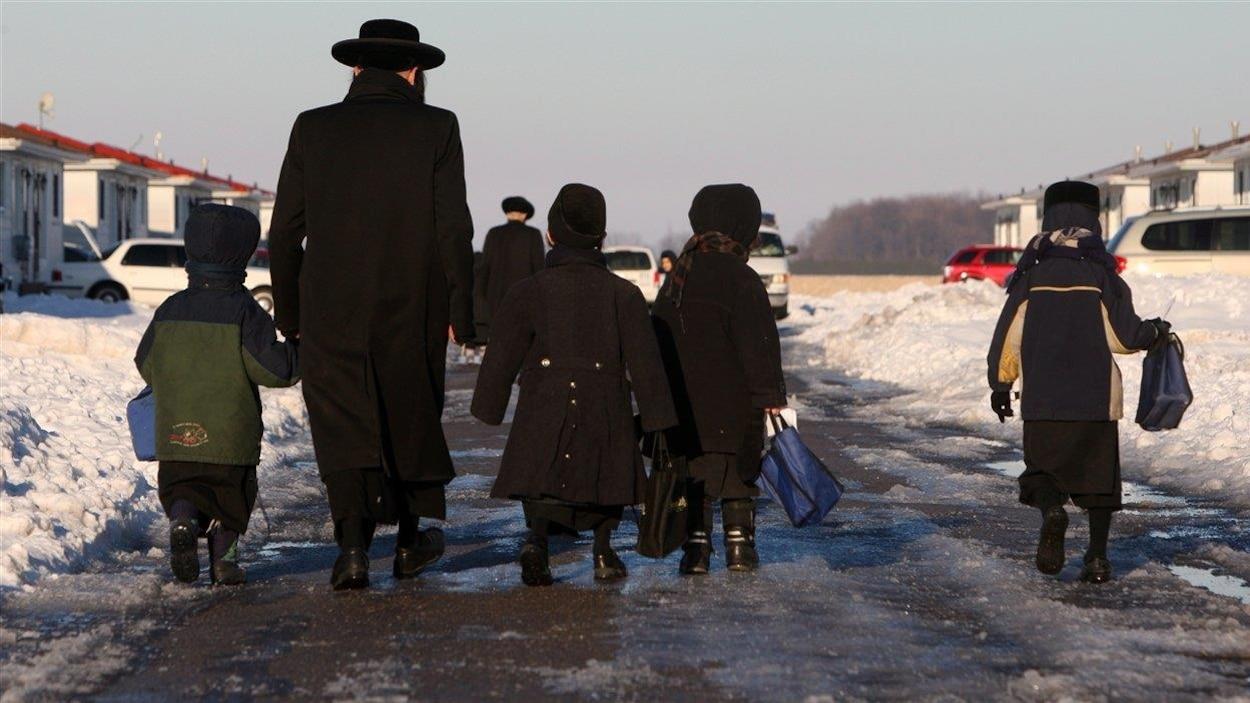 Des enfants et un adulte membres de la secte Lev Tahor marchent dans la neige.