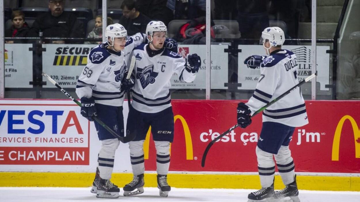 Trois joueurs de l'Océanic se félicitent sur la glace.