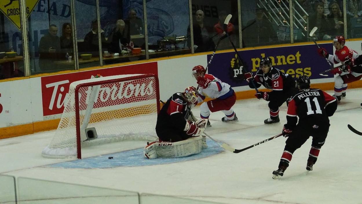 Une mêlée de hockeyeurs devant le filet du Canada où vient d'entrer la rondelle.