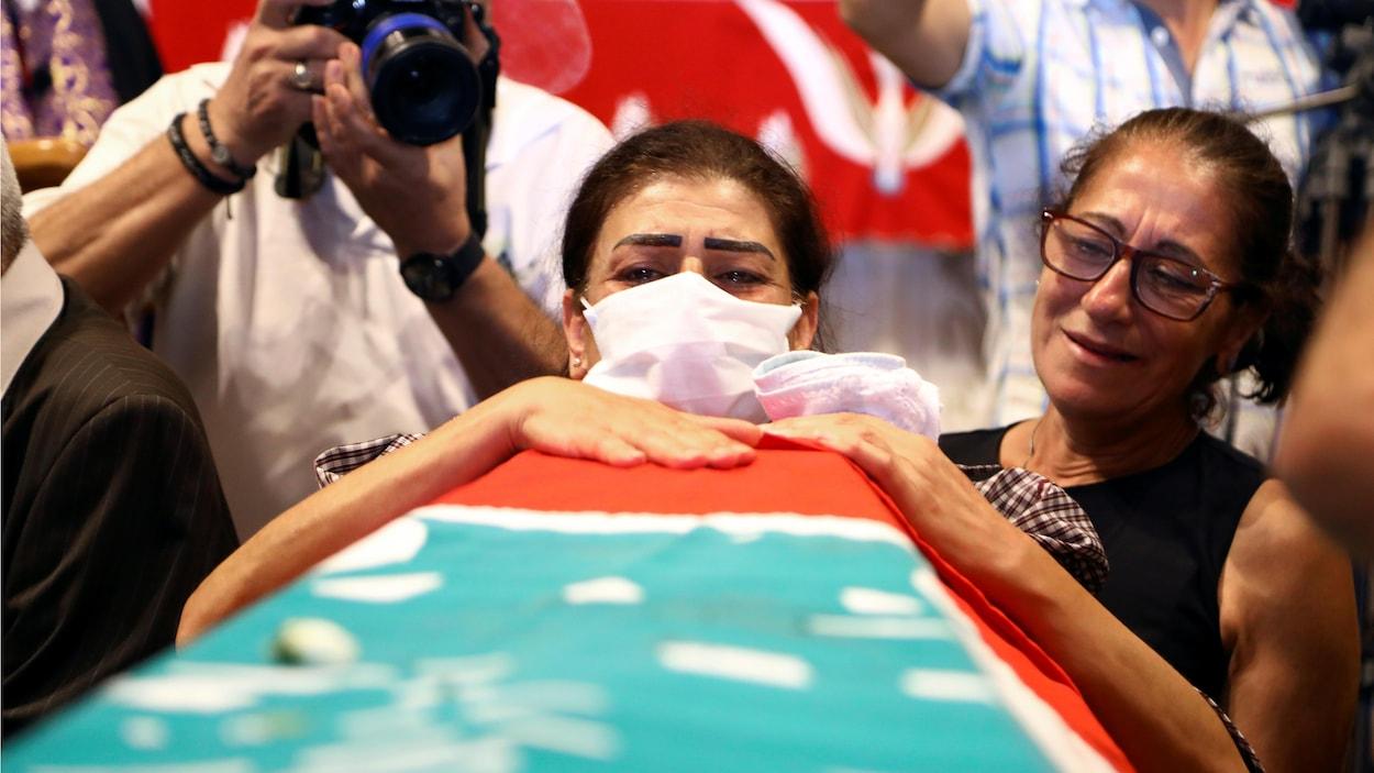 Une femme portant un masque pleure au-dessus d'un cercueil recouvert du drapeau libanais.