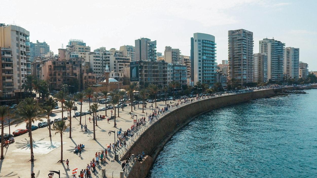 Une photo aérienne montre une file de milliers de personnes se tenant par la main, le long d'un quai qui borde la Méditerranée à Beyrouth, au Liban.