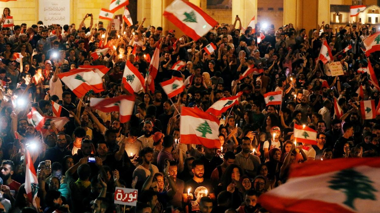 Une foule compacte brandissant des drapeaux du Liban dans une rue.