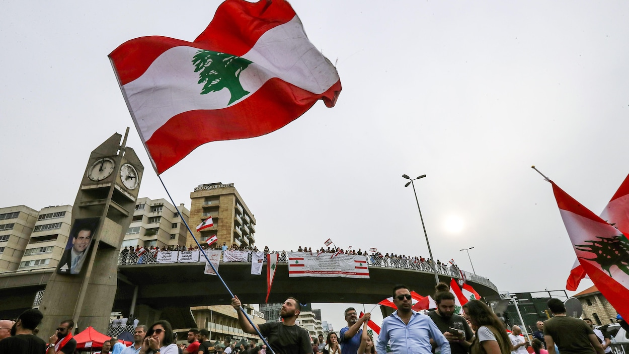 Un homme agite dans les airs le drapeau du Liban. Derrière lui se trouvent des dizaines de personnes, dont certaines sur un pont, qui tiennent des drapeaux libanais et des banderoles.