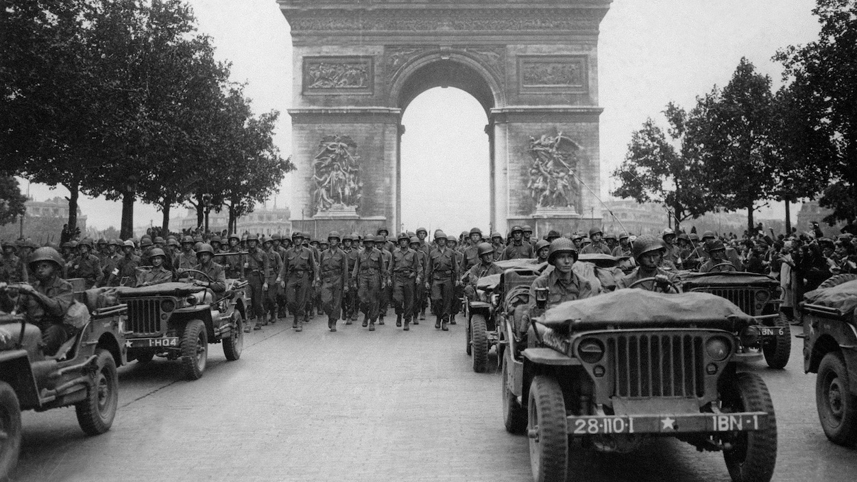 Photographie en noir et blanc d'une parade militaire sous l'Arc de Triomphe avec des soldats et des voitures.