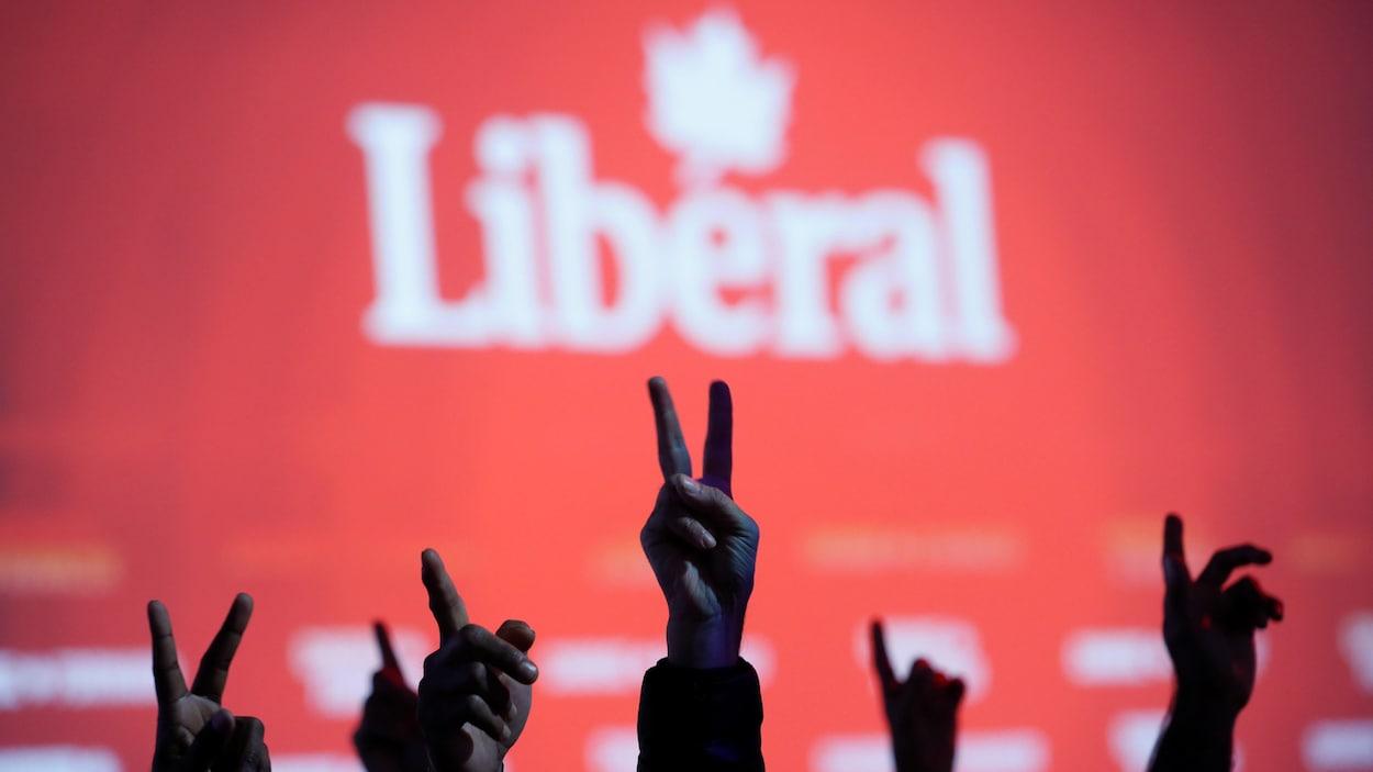 Des partisans libéraux font le signe de la victoire lors d'un rassemblement le soir des élections.