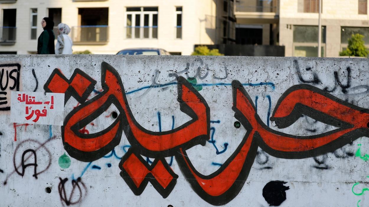 Un graffiti représentant une calligraphie arabe peinte en rouge et noir.