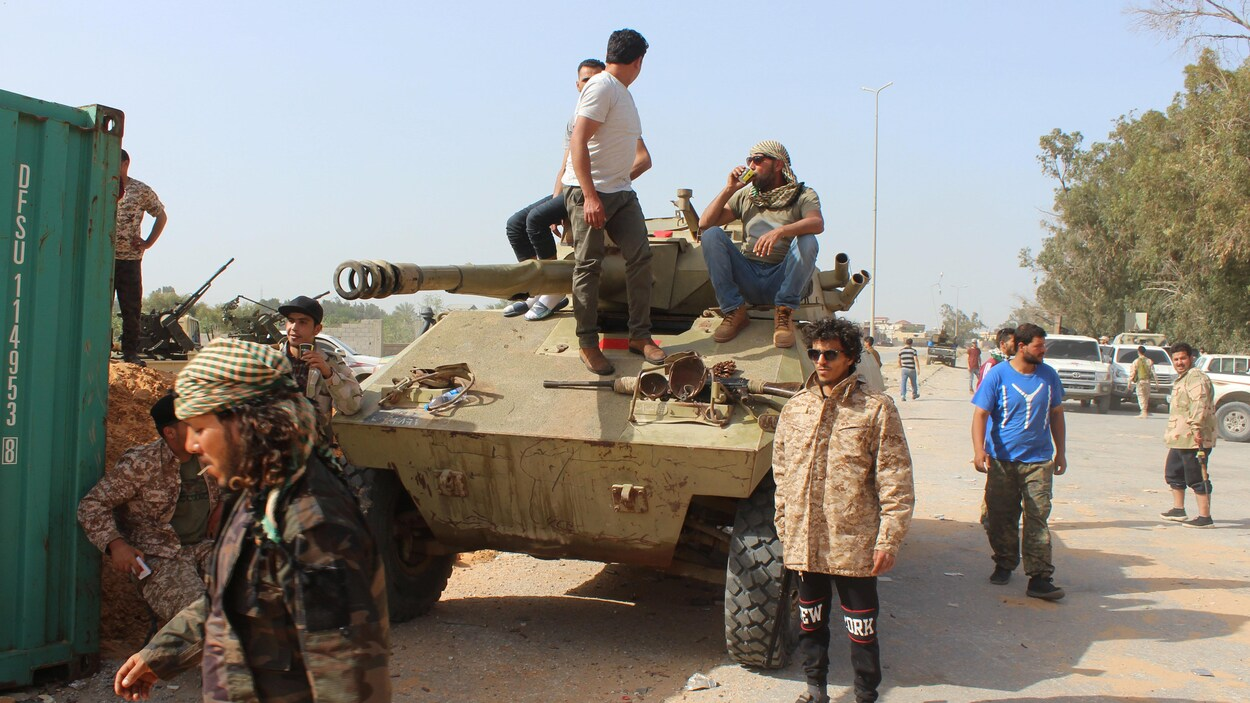 Des membres du gouvernement libyen reconnu par la communauté internationale entourent un blindé stationné non loin de la capitale, Tripoli.