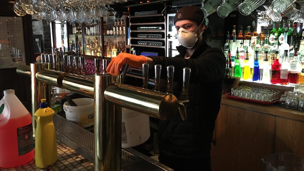 Un homme avec un masque et des gants active un fût de bière dans un bar.