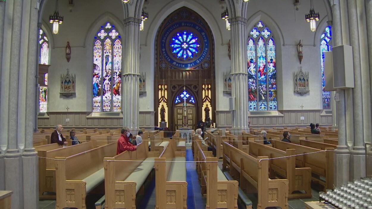 Des fidèles prient avec des masques à l'intérieur de la cathédrale St. Michael's à Toronto.